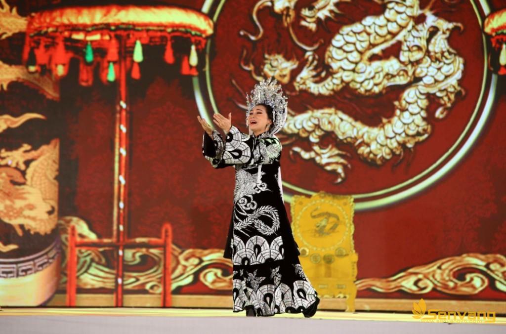 """NSND Bạch Tuyết xuất hiện trong tiếng vỗ tay đón chào của đông đảo khán giả. Ngay sau đó không gian lắng lại khi nghệ sĩ cất tiếng ca thể hiện trích đoạn cải lương """"Hoàng hậu hai vua"""" của soạn giả Lê Duy Hạnh."""