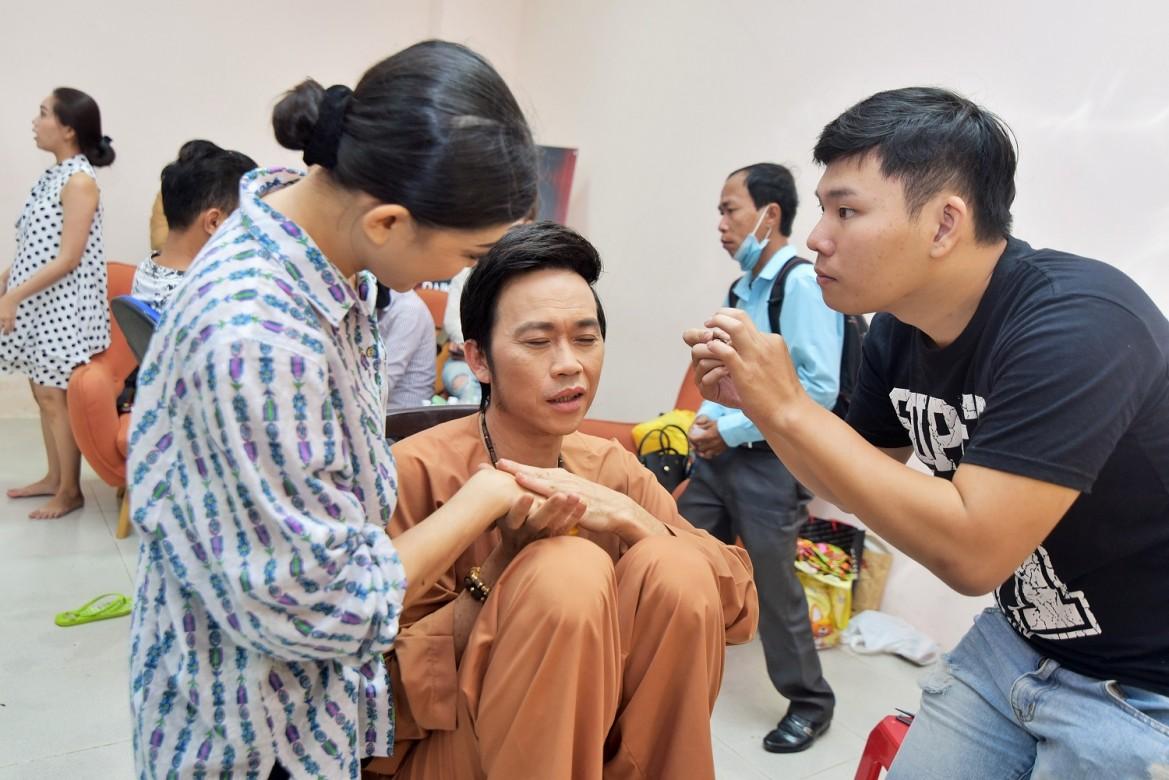 Tuy đang được make - up, Hoài Linh không quên nắm tay động viên thí sinh Hồng Trang.